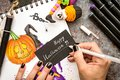 Female hands with black nails drawing halloween illustration with markers on wooden table top view Royalty Free Stock Photo