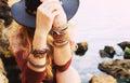 Female hands with boho chic bracelets holding black hat Royalty Free Stock Photo