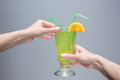 The female hands with cocktail on gray background Royalty Free Stock Photo