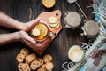 Female hands holding cup black tea with lemon, ginger and cookies on dark wood Royalty Free Stock Photo