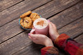 Female hands holding cup of coffee and cookies on wooden table Royalty Free Stock Images