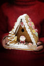 Female hands holding festive gingerbread house Stock Photo