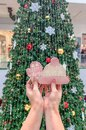 Female hands holding ginger cookies in the form of a hat and mittens, against the background of the Christmas tree