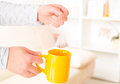 Female hands holding tea bag over the yellow mug Royalty Free Stock Images