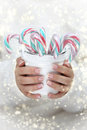 Female hands holding white bucket with candy canes Stock Photo