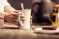 Female hands holding a white cup of tea standing close to wooden desk. Royalty Free Stock Photo