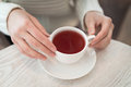 Female hands holding a white cup of tea standing on the table top view Royalty Free Stock Photo
