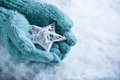Female hands in light teal knitted mittens with entwined white star on a white snow background. Winter and Christmas concept Royalty Free Stock Photo