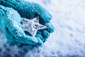 Female hands in light teal knitted mittens with entwined white star on a white snow background. Winter and Christmas concept. Royalty Free Stock Photo
