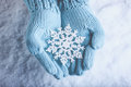 Female hands in light teal knitted mittens with sparkling wonderful snowflake on snow background. Winter and Christmas concept Royalty Free Stock Photo