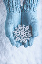Female hands in light teal knitted mittens with sparkling wonderful snowflake on a white snow. Winter and Christmas concept. Royalty Free Stock Photo