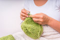 Female hands with needles knitting with green wool Royalty Free Stock Photo