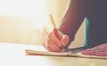 Photo : Female hands with pen writing   bokeh