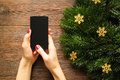 Female hands with red manicure holding a mobile phone with a tou touch screen on the background of christmas decorations view from Stock Photos
