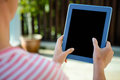 Female hands scrolling on a tablet computer in garden Stock Image