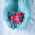 Female hands in teal knitted mittens with a entwined vintage romantic heart on a snow background love and st valentine concept Stock Image