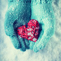 Female hands in teal knitted mittens with a entwined vintage romantic heart on a snow love and st valentine concept background Stock Images