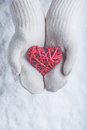 Female hands in white knitted mittens with entwined vintage romantic red heart on snow background love and st valentine concept a Stock Image