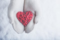 Female hands in white knitted mittens with entwined vintage romantic red heart on snow background love and st valentine concept a Royalty Free Stock Images
