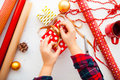 Female hands wrapping xmas gifts into paper and tying them up wi