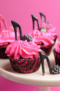 Female high heel stiletto shoes decorated pink and black red velvet cupcakes - close up on black cupcake. Royalty Free Stock Photo