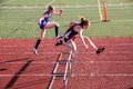 Female high school track athletes clear hurdles in 300 meter hurdle race Royalty Free Stock Photo