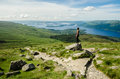 Female hiker admiring the landscape on a path leading to the top Royalty Free Stock Photo