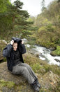 Female hiker near river sheltering from the rain Stock Photo