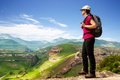 Female hiker on rocky cliff young hiking tourist contemplating open view Royalty Free Stock Photography