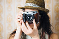 Female hipster taking photo with retro camera woman photos film on vintage ornamental wallpaper Stock Photography