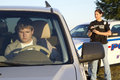 Female hispanic police officer writes a ticket focus driver young caucasian male as Royalty Free Stock Images