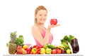 Female holding an apple and posing behind a table full of vegate young smiling red vegatebles fruits isolated against white Stock Photography