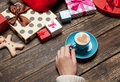 Female holding cup of coffee on wooden table near christmas gifts Royalty Free Stock Photos