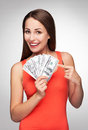 Female holding a fan of money casual young woman over grey background Royalty Free Stock Photography