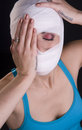 Female holds face first aid gauze wrapped head injury pain woman in eyes closed holding Stock Photos