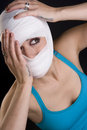Female holds face first aid gauze wrapped head injury pain woman in eyes closed holding Stock Photo