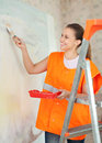 Female house painter paints wall Royalty Free Stock Image