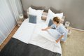 Female housekeeper changing bedding young in hotel room Stock Images