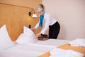 Female housekeeper making bed in hotel room young Royalty Free Stock Photos