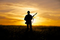 A female hunter silhoutted against a dramatic sunset with rifle Royalty Free Stock Photos
