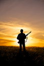 A female hunter silhoutted against a dramatic sunset with rifle Royalty Free Stock Images
