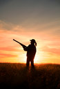 Female hunter in sunset a bird silhoutted against a dramatic with shotgun Royalty Free Stock Image