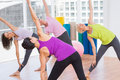 Female instructor guiding friends in stretching exercise at gym Stock Photo
