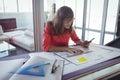 Female interior designer making plans on papers