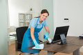 Female Janitor Cleaning Desk
