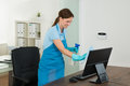 Female Janitor Cleaning Desk Royalty Free Stock Photo