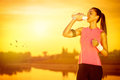 Female jogger drinking water thirsty from bottle Royalty Free Stock Image
