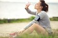 Female jogger resting and drinking bottled water tired sitting on the grass Royalty Free Stock Photography