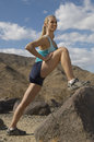Female Jogger Stretching On Rock Royalty Free Stock Photography