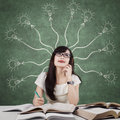 Female learner and branchy light bulb image of a smart college student studying in the classroom thinks idea with a on the Royalty Free Stock Photography